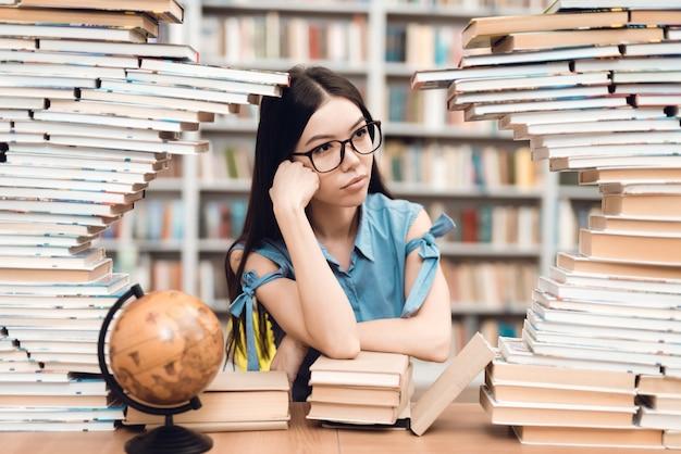 Etniczny Azjatykci Dziewczyny Obsiadanie Przy Stołem Otaczającym Książkami W Bibliotece. Premium Zdjęcia