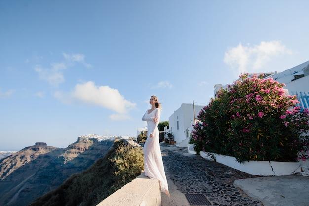 Europa Grecja Santorini Podróży Wakacje. Kobieta Patrzeje Widok Na Sławnym Podróży Miejscu Przeznaczenia. Elegancka Młoda Dama żyjąca Stylem Fantazyjnym Odrzutowym Ubrana W Sukienkę Na święta. Niesamowity Widok Na Morze I Kalderę Premium Zdjęcia
