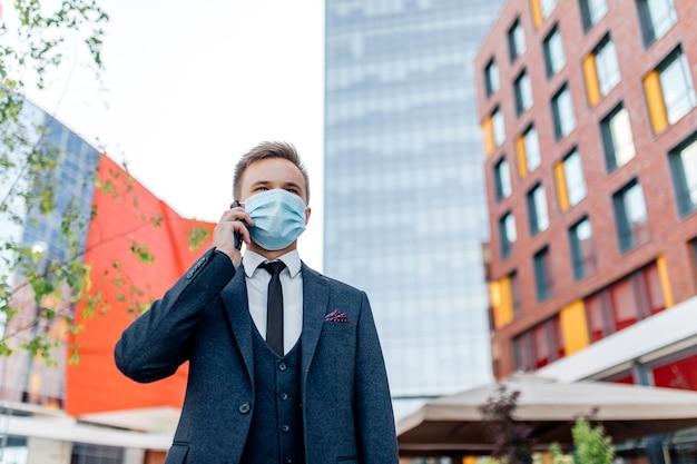 Europejczyk Noszący Chirurgiczną Maskę Na Twarz Za Pomocą Smartfona W Mieście, Premium Zdjęcia