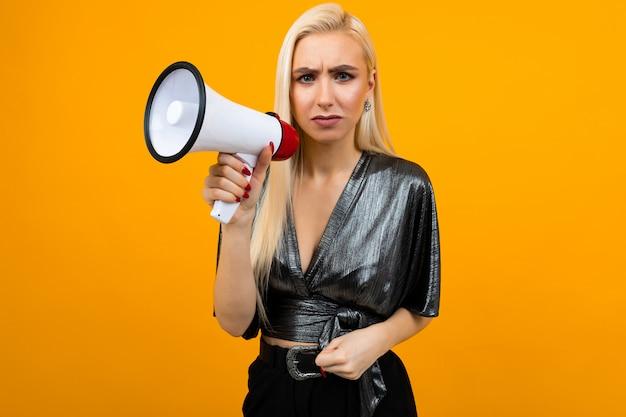 Europejska Blond Dziewczyna W Grafitowej Bluzce Z Megafonem W Dłoniach Na Baner Informacyjny Na żółtej ścianie Premium Zdjęcia