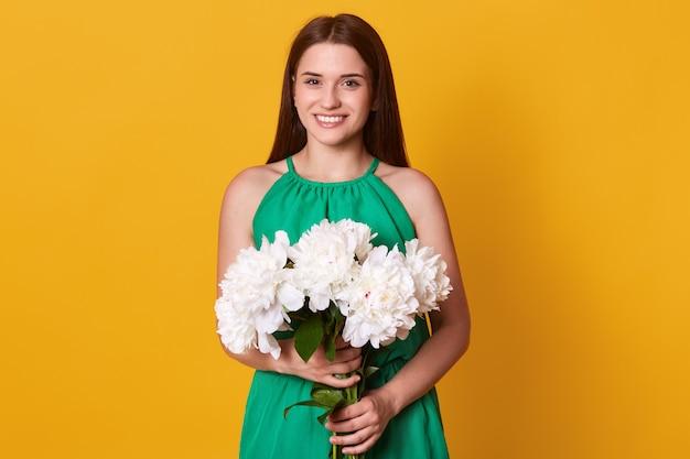 Europejska Brunetka Kobieta Ubrana W Zieloną Sukienkę Z Bukietem Białych Piwonii Kwitnie W Obu Rękach, Pozując Na żółto, Będąc W świetnym Humorze. Koncepcja Sping. Darmowe Zdjęcia