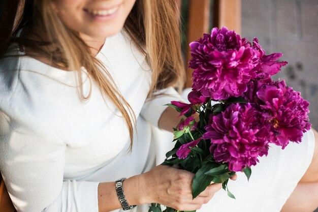 Europejska dziewczyna z kwiatami, piwonie w dłoniach Premium Zdjęcia