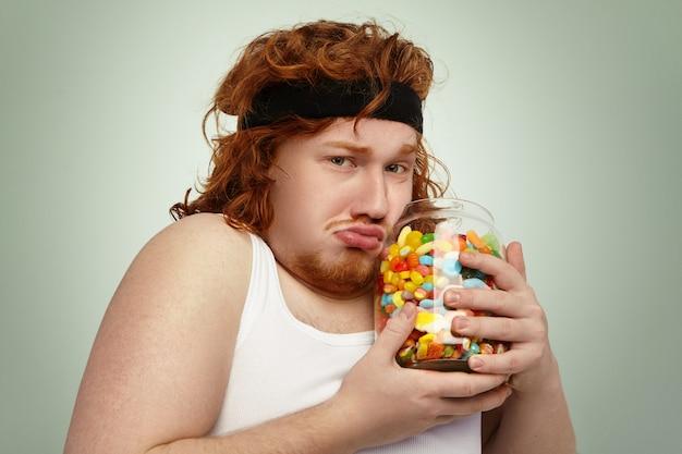Europejski Mężczyzna Z Nadwagą W Opasce Do Włosów I Podkoszulku Fitness Po Intensywnym Treningu Cardio, Usiłujący Walczyć Z Nadwagą, Wyglądający Na Nieszczęśliwego, Trzymający W Rękach Duży Słoik Zakazanych Cukierków Darmowe Zdjęcia