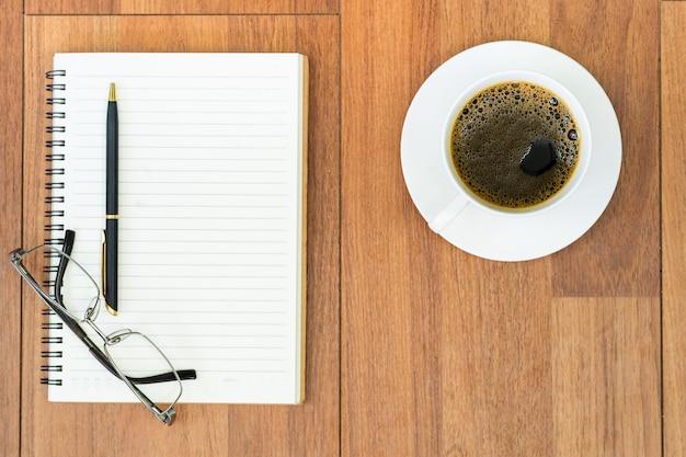 Eyeglasse I Notatnik Z Filiżanką Kawy Na Pokładzie Drewna Premium Zdjęcia