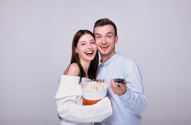 Facet i kobieta z pilotem telewizora jedzą popcorn. Premium Zdjęcia