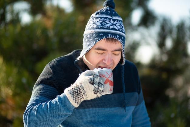 Facet pije gorący napój z piankami w zimie w lesie, przytulny zimowy spacer po lesie z gorącym napojem, z pianki z napojem jest pianka, śmieszne zdjęcie Premium Zdjęcia