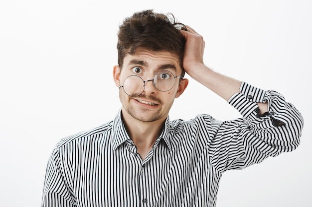 Facet Po Kacu Stracił Pamięć. Zdezorientowany Zapytany Niechlujny Mężczyzna W Koszuli W Paski, Drapiąc Się Po Włosach I Wyglądający Na Nieświadomego I Nieświadomego Spojrzeniem Spod Okularów, Stojący Nad Szarą ścianą Darmowe Zdjęcia