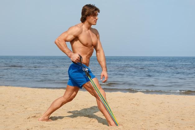 Facet Pracujący Z Gumką Na Plaży Premium Zdjęcia