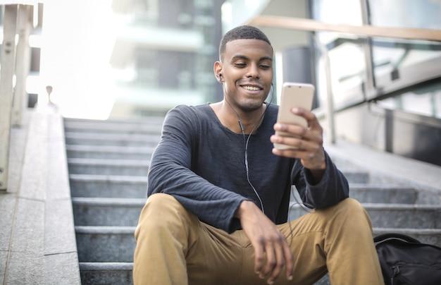 Facet siedzący na schodach, patrząc na swój telefon i śmiejący się Premium Zdjęcia