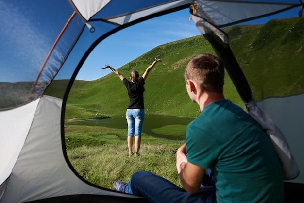 Facet Siedzi W Namiocie, A Jego Dziewczyna Cieszy Się Widokiem Czystego Jeziora U Podnóża Potężnej Zielonej Góry Pod Niebieskim Niebem. Widok Z Wnętrza Namiotu Premium Zdjęcia