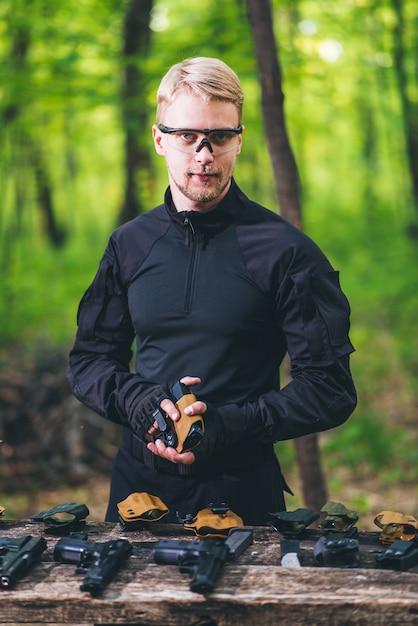 Facet w lesie testuje swoją broń do strzelania do sportu Premium Zdjęcia