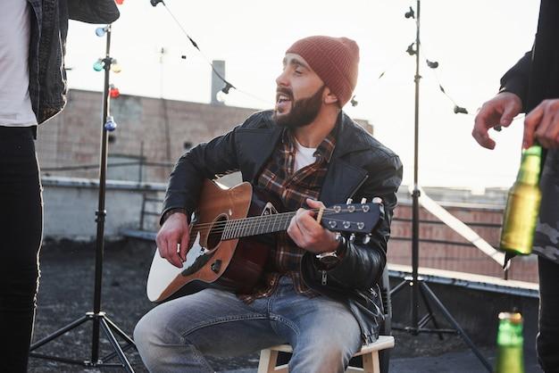 Facet Z Gitarą Akustyczną śpiewa. Przyjaciele Bawią Się Na Imprezie Na Dachu Z Dekoracyjnymi Kolorowymi żarówkami Darmowe Zdjęcia