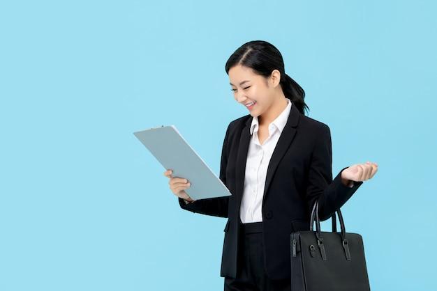 Fachowy Azjatycki Bizneswoman Patrzeje Schowek W Formalnym Kostiumu Premium Zdjęcia
