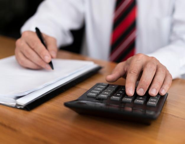 Fachowy mężczyzna pisać na maszynie liczby na kalkulatorze Darmowe Zdjęcia