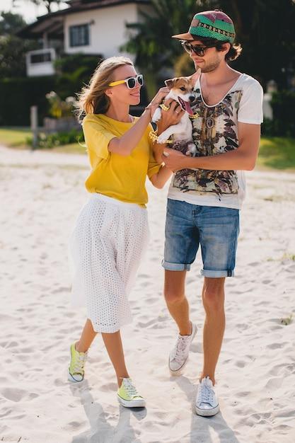 Fajna Młoda Stylowa Hipster Zakochana Para Spacerująca Grająca Psa Szczeniaka Jack Russell Na Tropikalnej Plaży, Biały Piasek, Romantyczny Nastrój, Dobra Zabawa, Słonecznie, Mężczyzna Kobieta Razem, Wakacje Darmowe Zdjęcia