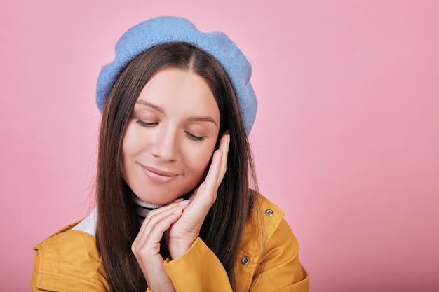 Fajna śliczna dziewczyna w żółtej kurtce przeciwdeszczowej uśmiecha się zamknięte oczy Premium Zdjęcia