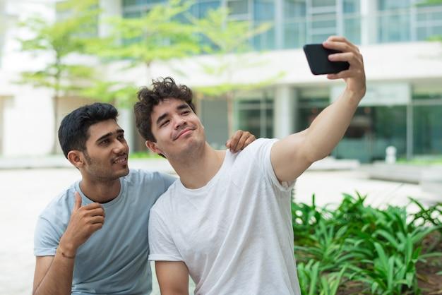Fajni przystojni faceci fotografuje na frontowej kamerze smartphone Darmowe Zdjęcia