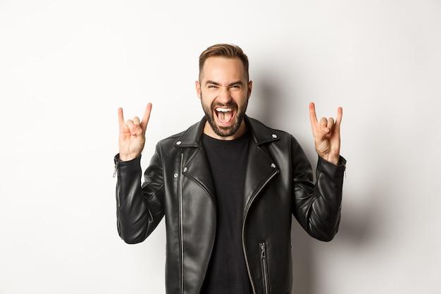 Fajny Dorosły Mężczyzna W Czarnej Skórzanej Kurtce, Pokazujący Rock Na Geście I Języku, Ciesząc Się Festiwalem Muzycznym, Stojąc Darmowe Zdjęcia