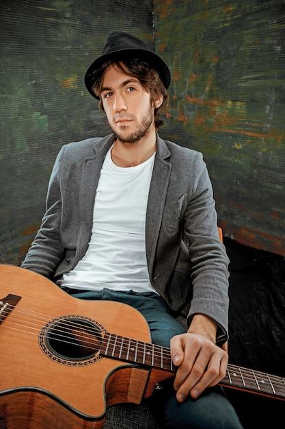 Fajny Facet Siedzący Z Gitarą Na Szaro Darmowe Zdjęcia