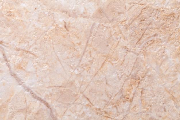 Faktura Dekoracyjnego Tynku W Kolorze Beżowym Imitującym Stary łuszczący Się Mur. Przestarzałe Kremowe I Brązowe Pęknięte Tło, Zbliżenie. Premium Zdjęcia