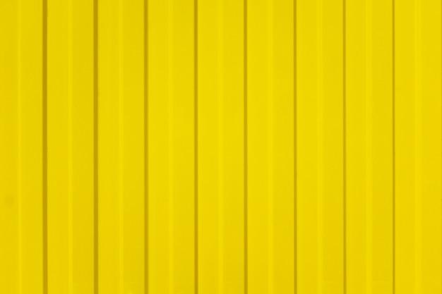 Faliste ogrodzenie z żółtych blach ze śrubą. tekstura metalowe ogrodzenie Premium Zdjęcia