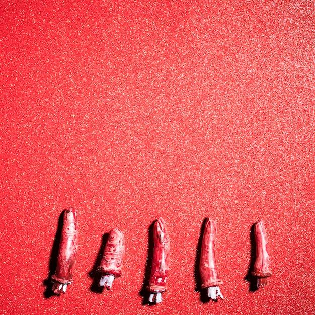 Fałszywe Straszne Palce Na Tle Czerwonego Brokatu Darmowe Zdjęcia