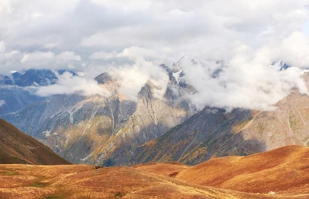Fantastyczne Ośnieżone Góry W Pięknych Chmurach Cumulus. Główny Grzbiet Kaukaski. Wpisz Mount Ushba Meyer, Georgia Premium Zdjęcia