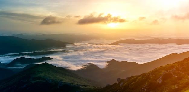 Fantastyczny Widok Na Górską Dolinę Pokrytą Niskimi Białymi Puszystymi Jak śnieg Chmurami Sięgającymi Mglistego Horyzontu Premium Zdjęcia