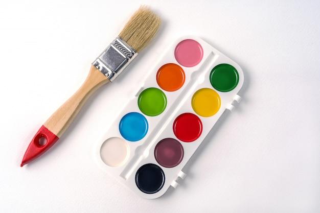 Farby akwarelowe w białym polu i pędzlem, na białym tle Premium Zdjęcia