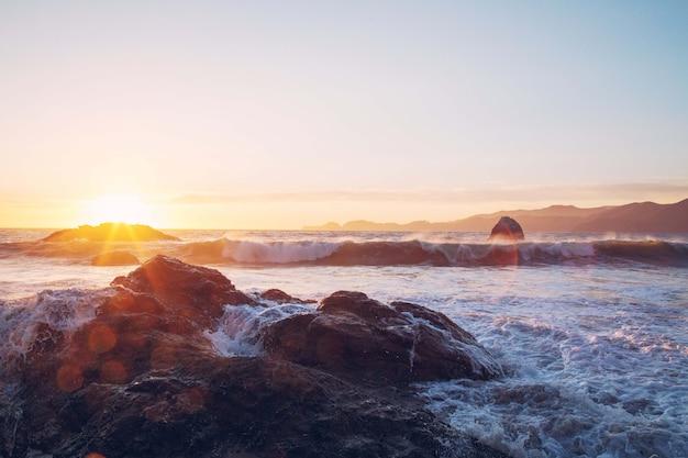 Fascynujący Widok Fal Oceanu Rozbijających Się O Skały W Pobliżu Brzegu Podczas Zachodu Słońca Darmowe Zdjęcia