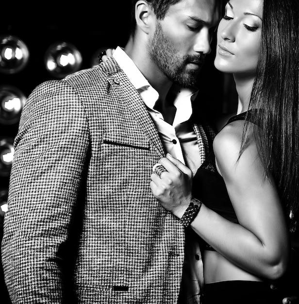 Fasonuje Fotografię Przystojny Elegancki Mężczyzna W Kostiumu Z Piękną Seksowną Kobietą Pozuje Na Czarnym Studiu Zaświeca Tło Darmowe Zdjęcia