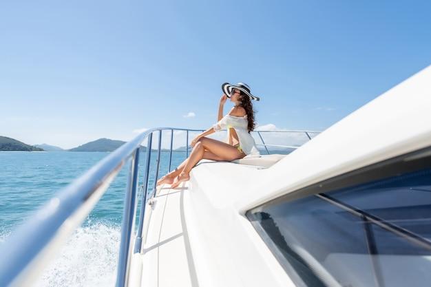 Fasonuje Fotografię Urocza Młoda Kobieta Siedzi Na Krawędzi Luksusowego Jachtu I Patrzeje Morze Podczas żeglowanie Wycieczki Premium Zdjęcia