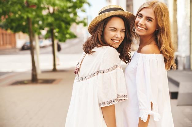 Fasonuje Portret Dwa Młodego Eleganckiego Hipisa Brunetki I Blondynów Kobiet Modeluje W Lato Słonecznym Dniu W Biały Modnisia Odzieżowy Pozować. Bez Makijażu Darmowe Zdjęcia