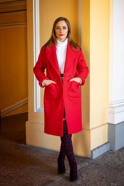 Feshion kobieta w czerwonej kurtki pozyci na ulicie Premium Zdjęcia