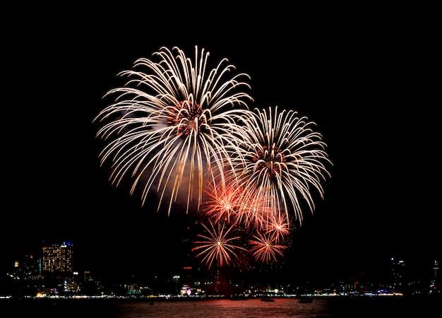 Festiwal fajerwerków w pattaya, tajlandia. kolorowi fajerwerki na nocnym niebie przy plażą. Premium Zdjęcia