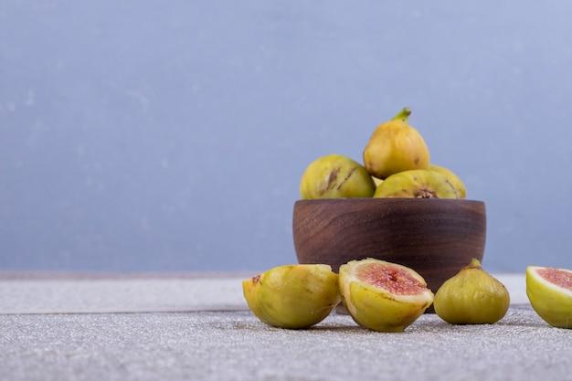 Figi Całe I Pokrojone W Drewnianej Misce I Na Białym Stole. Darmowe Zdjęcia