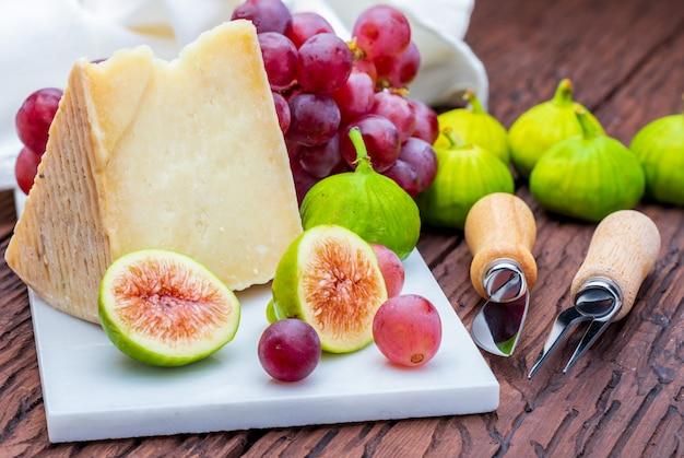 Figi, Czerwone Winogrona I Ser Owczy (typ Manchego). Na Białym Marmurze I Drewnie. Premium Zdjęcia