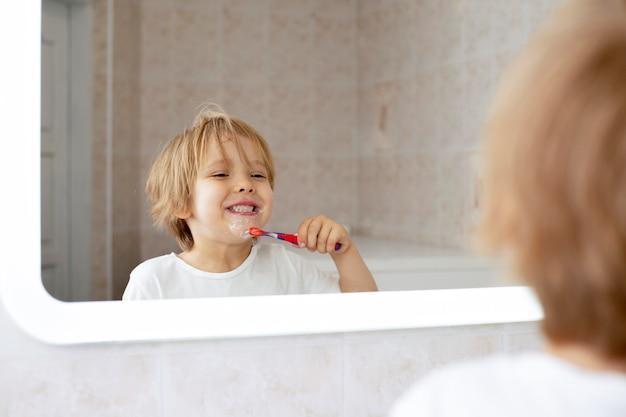 Figlarny Chłopiec Szczotkuje Zęby Premium Zdjęcia