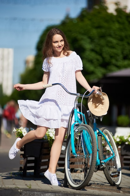 Figlarny Dziewczyna W Słońcu Letniego Dnia Z Niebieskim Retro Rower Na Ulicy Miasta. Premium Zdjęcia