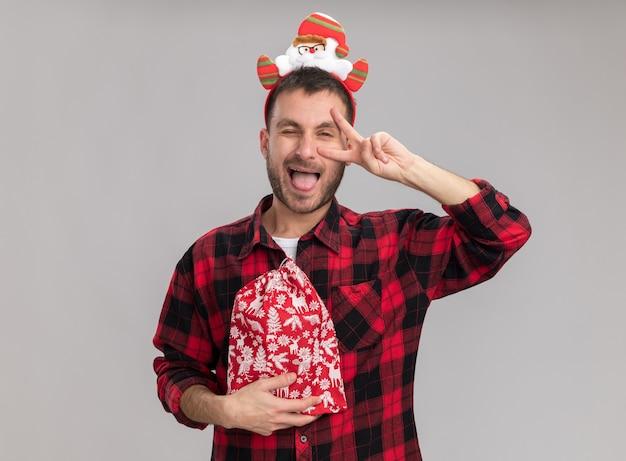 Figlarny Młody Kaukaski Mężczyzna Ubrany W świąteczną Opaskę Trzymającą świąteczny Worek Patrząc Na Kamery Pokazujący Symbol V-znak W Pobliżu Oczu Mrugający Na Białym Tle Darmowe Zdjęcia