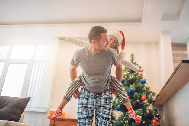 Figlarny Obrazek Przedstawiający Szczęśliwego Ojca I Córkę Spędzających Razem Czas. Ujeżdża Ją Na Plecach. Premium Zdjęcia