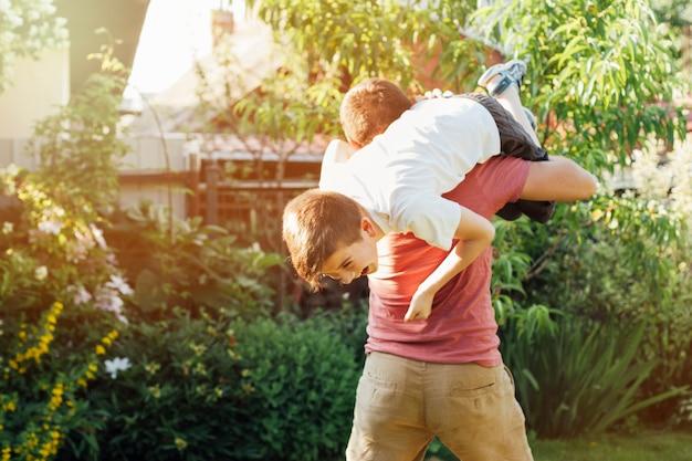 Figlarny ojciec niesie jego uśmiechniętego syna na ramieniu w parku Darmowe Zdjęcia