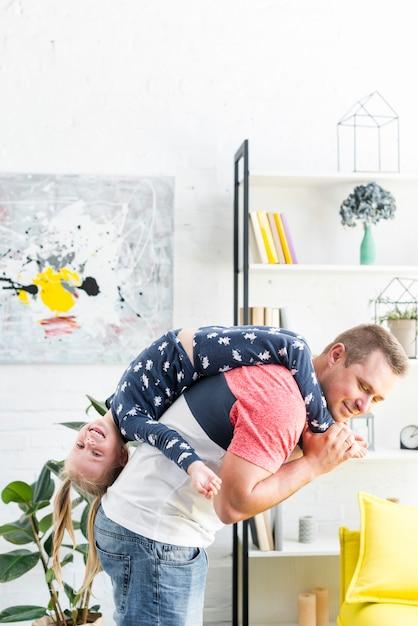 Figlarny ojciec niosąc jej szczęśliwą córkę w salonie Darmowe Zdjęcia