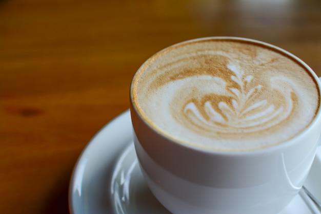 Filiżanka Cappuccino Kawa Z Latte Sztuką Na Drewnianym Tle Serw W Kawiarni Premium Zdjęcia