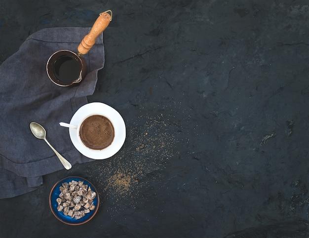 Filiżanka czarnej kawy z wysuszonymi figami i cukierem trzcinowym nad zmroku kamieniem, odgórny widok Premium Zdjęcia
