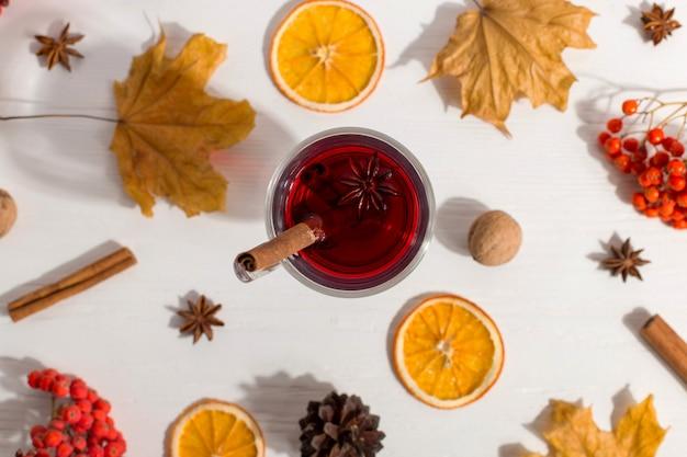 Filiżanka grzanego wina z przyprawami, suchymi liśćmi i pomarańczami na stole. jesienny nastrój, metoda na ogrzanie się w zimnym, porannym świetle, na płasko. Premium Zdjęcia