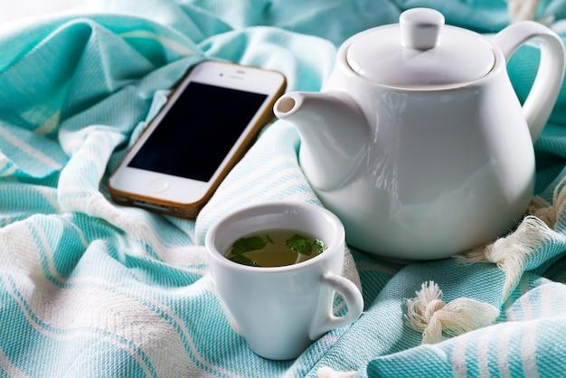 Filiżanka herbaty i telefon komórkowy w łóżku z czajnikiem na niebieskiej kratce Premium Zdjęcia