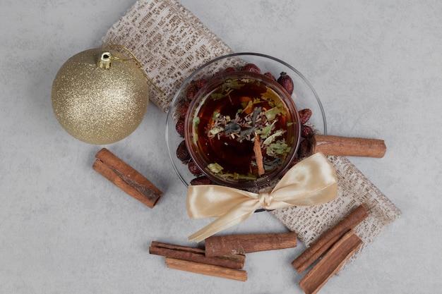 Filiżanka Herbaty, Laski Cynamonu I świąteczna Piłka Na Białym Stole. Wysokiej Jakości Zdjęcie Darmowe Zdjęcia