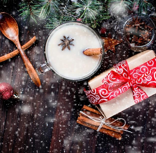 Filiżanka Herbaty Z Mlekiem I Cynamonem, Jodła, Szyszki, Kakao W Czerwonym Kubku Premium Zdjęcia