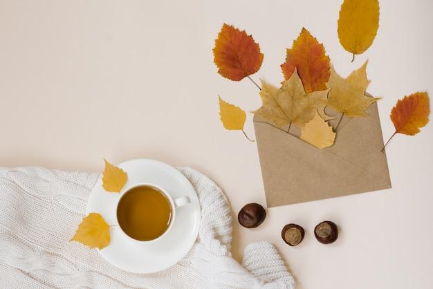 Filiżanka Herbaty Ze Spodkiem, Jesienne Suche Jasne Liście, Koperta Kraft, Kasztany, Biała Dzianinowa Kratka Na Jasnym Beżowym Tle Widok Z Góry Premium Zdjęcia